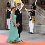 Prinz Joachim und Prinzessin Marie von Dänemark schreiten lächelnd auf dem roten Teppich zur Kirche.