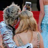 Paris Hilton und ihr Gast schießen auf dem roten Teppich ein Erinnerungsfoto. Das gehört in Cannes dazu.