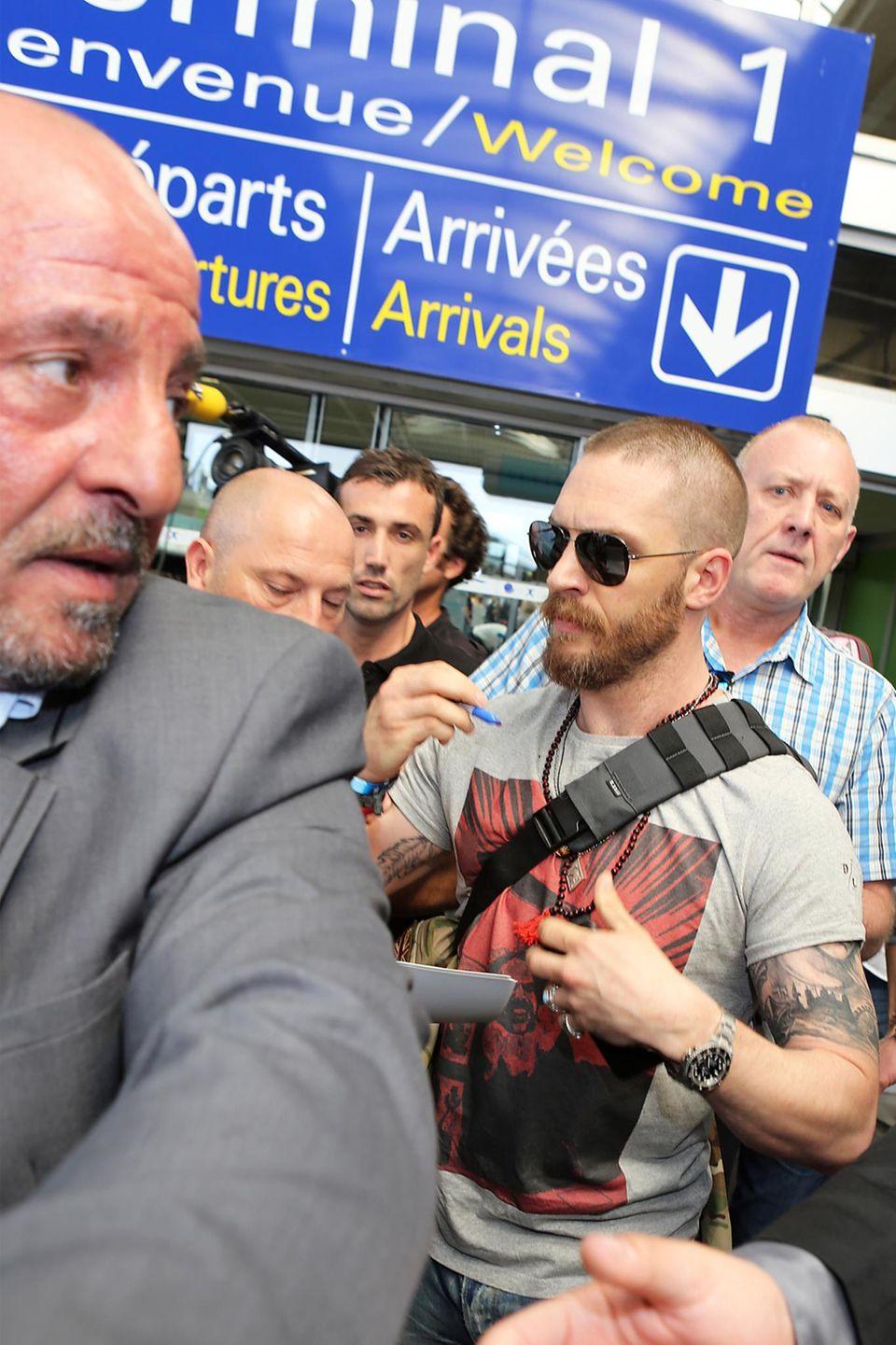 Schauspieler Tom Hardy kämpft sich am Flughafen durch die Massen und gibt noch schnell ein paar Autogramme.