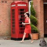 Das Kleid dieser Dame harmoniert perfekt mit der roten Tefonzelle.