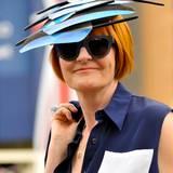 Eine äußerst kreative Hutkreation, den Kopf einer Dame schmücken überdimensionale blaue Federn.