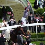 Jockey Frankie Dettori springt vor Freude vom Pferd.