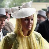 Das Wetter macht erfinderisch, diese Besucherin trägt ihren Hut über dem Regencape.
