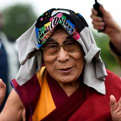Seine Heiligkeit der Dalai Lama zauberte den Festivalbesuchern ein Lächeln aufs Gesicht, und das nicht nur, weil er mit ungewöhnlichem Regenschutz etwas anders aussieht als üblich.