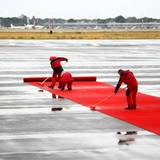 Tag 1  Regen in Berlin, ein paar Flughafenmitarbeiter rollen auf dem Flughafen Tegel in Berlin schon mal den roten Teppich auf dem nassen Boden aus.