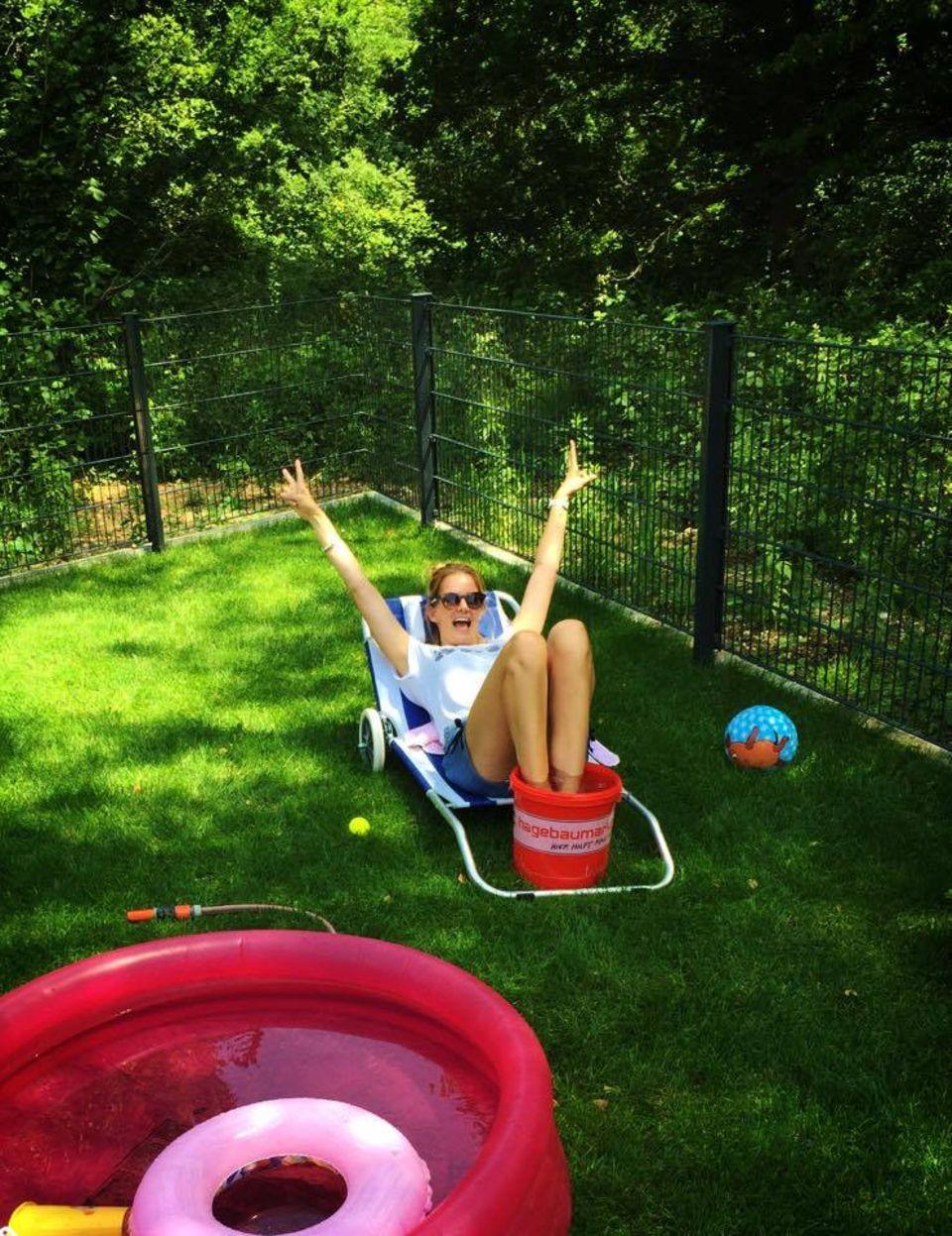 """Die bürgerliche Garten-Abkühlungsvariante stellt uns Monica Ivancan vor: Und schreibt dazu ganz süß:   """"Wer braucht nen Swimmingpool wenn man einen Eimer haben kann!!!! Passt auf Euch auf und trinkt genügend Wasser heute.  Bussi Moni Meier"""""""