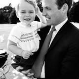 """Ein zuckersüßes Foto von Prinz William und Prinz George - sie spielen nach Charlottes Taufe im Garten von """"Sandringham House"""". Am Bildrand sieht man noch einen Teil des antiken Millson-Kinderwagens der Royals, in dem Charlotte zur Kirche gefahren wurde."""