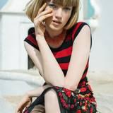 """Rot-schwarzes Stricktop mit kleinen Ärmeln, Pencilskirt aus Fishnet mit Blumenapplikationen, beides von Dolce & Gabbana. Korallenkette von Pebble London. Nagellack Nr. 24 """"Jaune Expression"""" von Givenchy"""