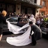 Zum Glück ist es nur ein kurzer Schreckmoment: Mit vereinten Kräften wird der Schleier befreit und die Braut sicher zum Wagen geleitet.