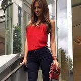 Fashion-Looks: Ihre Handtasche und Fußnägel stimmt Ann-Kathrin auf ihr leuchtend rotes Top ab. Als Kontrast stylt sie dazu eine dunkelblaue Jeans mit leichtem Schlag und silbernen Keilsandaletten.