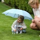 Prinzessin Estelle spielt hat Spaß mit dem Schirm und nutzt ihn lachend als Unterschlupf.