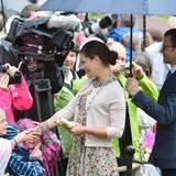 Während seine Frau Geschenke bekommt, hält Prinz Daniel ihr galant den Schirm.