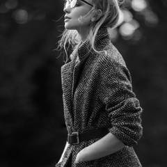 Schwarz-weißer Tweed-Kurzmantel von Basler. Brille von Prada. Ledergürtel von Mango.