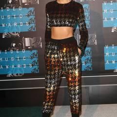 Dieses Jahr zeigt Taylor Swift Bauch und den funkelnden Metallic-Look. Das Hahnentritt-Muster ist ein zusätzlicher Eyecatcher. Dazu trägt sie ihre dunkelblonden Haare geschlossen und mit einem tiefen Seitenscheitel.