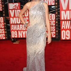 Taylor Swift glänzt bei den VMAs 2009 in einer silbernen One-Shoulder Robe. Mit ihren roten Lippen und der Hochsteckfrisur versprüht sie den klassischen Hollywood-Charme.