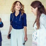 """Königin Rania macht sich ein Bild von den Vorbereitungen für die """"Amman Design Week"""", die am 1. September in der jordanischen Haupstadt Amman startet. Zu einer weißen Culotte kombiniert die Königin eine strahlend blaue Bluse mit raffinierten Stickereien."""