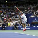Roger Federer steht gegen John isner auf dem Platz.
