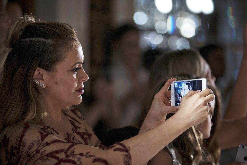 Alyssa Milano hält das Show-Finale von Marchesa auf ihrem Smartphone fest.