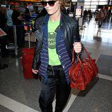 Vanessa Paradis trägt zum Fliegen eine lässige Kombination aus bequemer Hose und kuscheliger Strickjacke von Chanel. Der Hingucker ihres Outfits ist ihre knallrote Vintage-Handtasche.