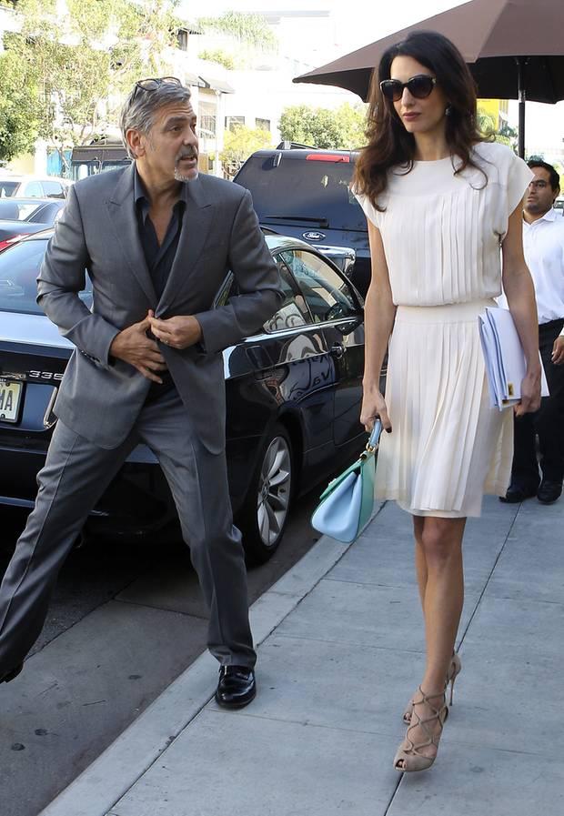 Für ein entspanntes Mittagessen mit ihrem Liebsten George Clooney hat sich Amal Clooney für ein weißes Plissee-Kleid entschieden, zu dem sie nudefarbene High-Heels und eine Handtasche von Dolce&Gabbana in Pastellfarben kombiniert.