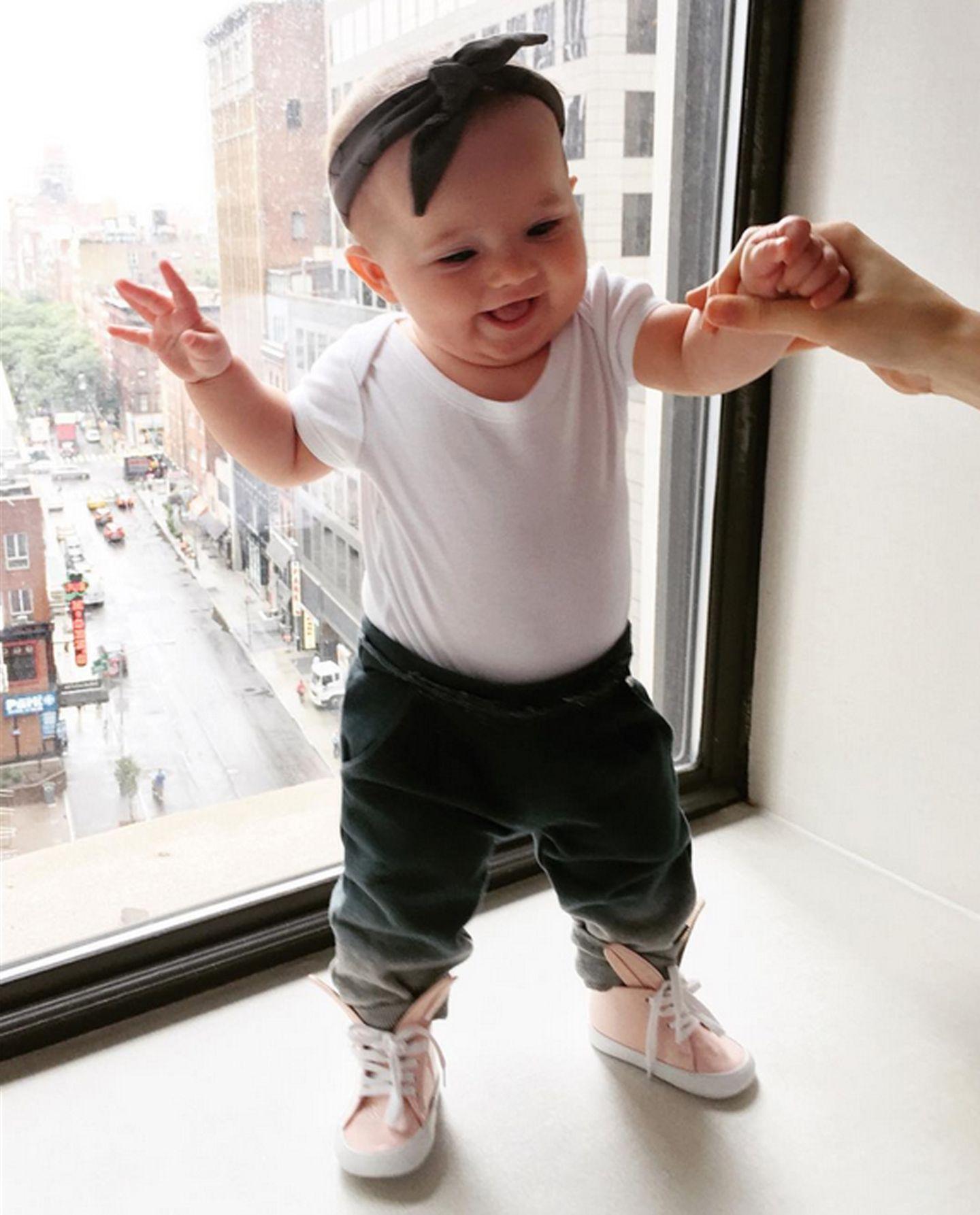 Einen lässigen Streetstyle mit farbigem Eyecatcher stellt das Outfit aus weißem Body, dunkelgrauer Jogginghose und rosafarbenen Leder-Sneakers dar, das Ioni Conran strahlend präsentiert.
