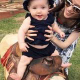 Ganz schön lässig, die kleine Reiterin! Im niedlichen, dunkelblauen Zweiteiler und mit passendem Stoffhütchen posiert Ioni Conran für ihre Eltern.