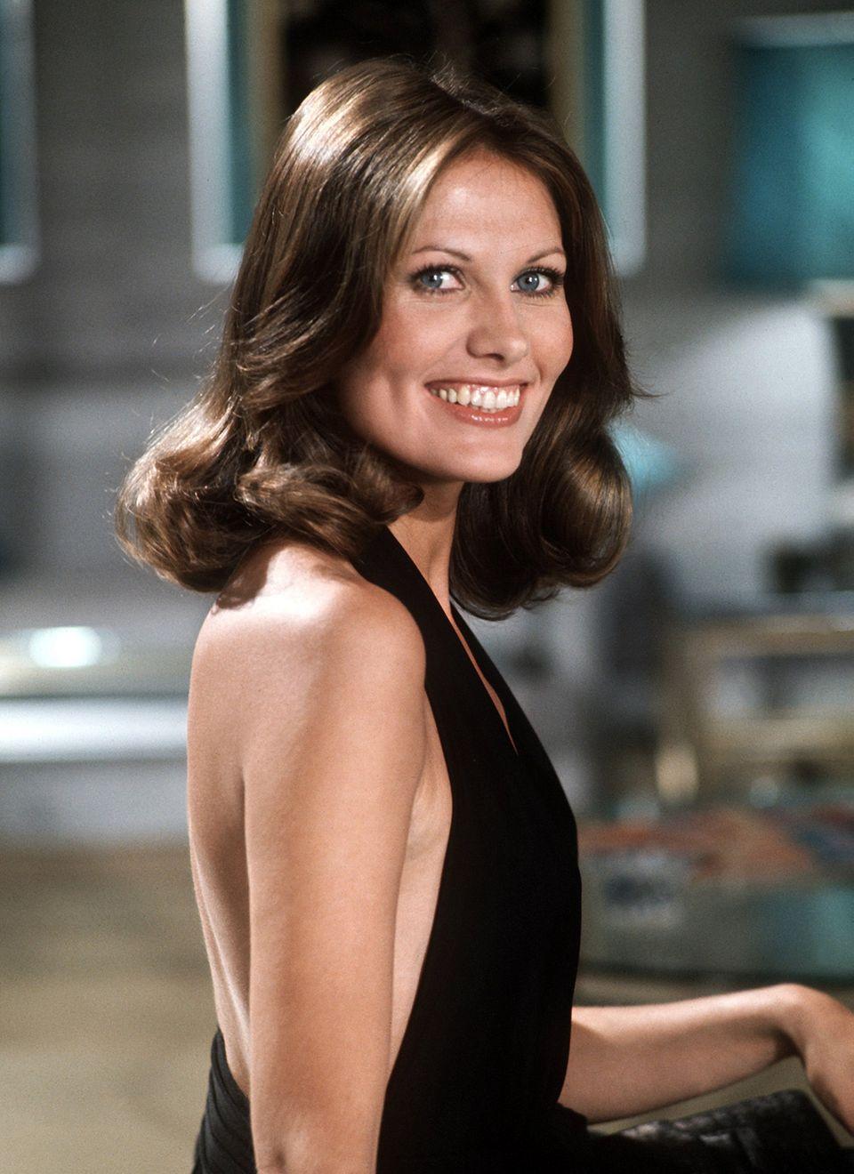 """Als """"Andrea Anders"""" trifft die brünette Maud Adams mit mittellangen, weichen Wellen 1974 auf Roger Moore als James Bond in """"Der Mann mit dem goldenen Colt""""."""