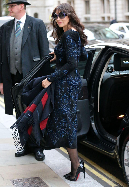 Wenn auch nicht ganz schwarz, so ist das Etuikleid mit Ornamentprint doch in tiefem Blau gehalten. Die farblich passende Sonnenbrille und Louboutin-Stilettos komplettieren Monica Belluccis Outfit.