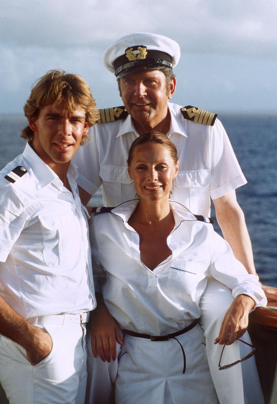 """Da war doch noch eine andere Serie?! Richtig! Sascha Hehn war nicht nur Lieblingsarzt. Er schipperte mit dem ZDF-""""Traumschiff"""" als Stewart """"Victor"""" über die Meere - und das noch vor seinem """"Schwarzwaldklinik""""-Einsatz. 2014 beförderte ihn das ZDF sogar und seither hat er als Kapitän das Kommando auf dem Seriendampfer. Den Schiffarzt spielt auch schon jemand anders ..."""