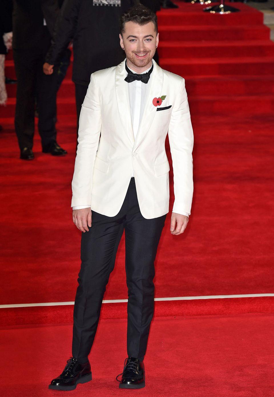 """Sam Smith hat den Titelsong """"Writing On The Wall"""" zum neuen James-Bond-Abenteuer beigesteuert und wählt für seinen großen Auftritt eine schwarze Anzughose zum weißen Dinnerjackett von Prada."""