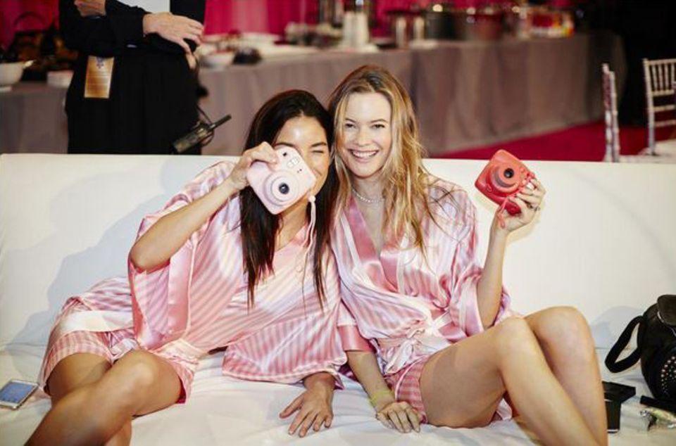 Damit auch wirklich jede Sekunde vor der Fashionshow dokumentiert und zur Erinnerung festgehalten wird, knipsen Lily Aldridge und Behati Prinsloo mit viel Freude ihre pinke Umgebung.