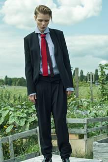 Anzug mit Schalkragen-Jackett und weiter Hose, von Marc Cain. Herrenhemd von Windsor. Zweifarbige Strickkrawatte mit Doppler-Effekt, von Hermès. Stiefeletten von Aquilano Rimondi