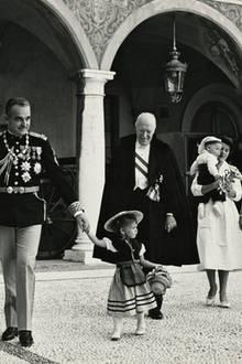 Die Fürstenfamilie strahlt beim Gang über den Schlosshof 1958. Prinzessin Caroline (an der Hand ihres Vaters) trägt wieder die Nationaltracht.