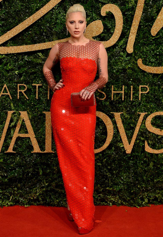 Lady Gaga trägt ein hochgeschlitztes klassisches Kleid von Tom Ford. Besonders auffällig: Die Netzapplikationen und -handschuhe
