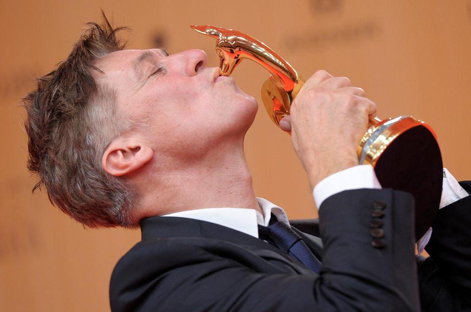 """Tobias Moretti küsst seine Auszeichnung in der Kategorie """"Schauspieler national""""."""