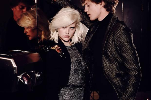 Anna trägt ein gestricktes Midi-Kleid von Hugo Boss aus schimmerndem Metallic-Garn, darüber einen Oversize-Blazer von Laurèl. Ohrringe: Iosselliani, Gürtel: Carven. Jonatan glänzt in einem schwarzgoldenen Jacquard-Blazer von Emporio Armani. Rollkragenpulli: Windsor, Smokinghose: H&M