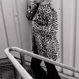 Anna hüllt sich in einen schwarz-weißen Fake-Fur Mantel mit Leoprint, von Guess. Darunter trägt sie einen Seiden-Anzug von Versace mit bunten Großbuchstaben. Stiefeletten: Dior