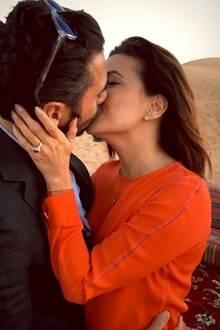 Hier sind die beiden Turteltauben vor ausgebreiteten Teppichen in der Wüste zu sehen, innig küssen sie sich. An ihrem Ringfinger funkelt deutlich sichtbar ihr Verlobungsklunker.