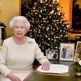 """24. Dezember: England  Queen Elizabeth spricht zu ihren Untertanen vom """"Buckingham Palace"""" aus. Zu ihrer Weihnachtsansprache sitzt sie an einem antiken Schreibtisch, au dem drei Bilder stehen: Ganz links zu erkennen ist ein Taufbild von Prinzessin Charlotte, ihrer jüngsten Urenkelin. In der Mitte steht das Hochzeitsbild von Prinz Charles und Herzogin Camilla und ganz rechts ein Bild, das die Monarchin und Prinz Philip zeigt."""