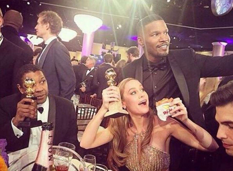 """Brie Larsons Freude über ihren """"Golden Globe"""" als beste Schauspielerin in einem Drama ist zwar groß, noch glücklicher macht sie jedoch ihr frischer Burger von In-N-Out. Zur Feier des Tages hat Katy Perry eine Sammelbestellung bei der Fast-Food-Kette aufgegeben und damit den gesamten Tisch samt Jamie Foxx überrascht."""