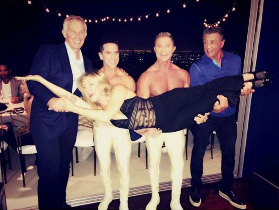 """Fragt Kate Hudson nicht, wie das plötzlich entstanden ist: Ex-Premierminister Tony Blair, zwei Muskelmänner vom Cirque du Soleil und Actionheld Sylvester Stallone tragen die schöne Blondine auf den Armen. Die Haltungsnote """"1+"""" vergeben wir aber trotzdem."""