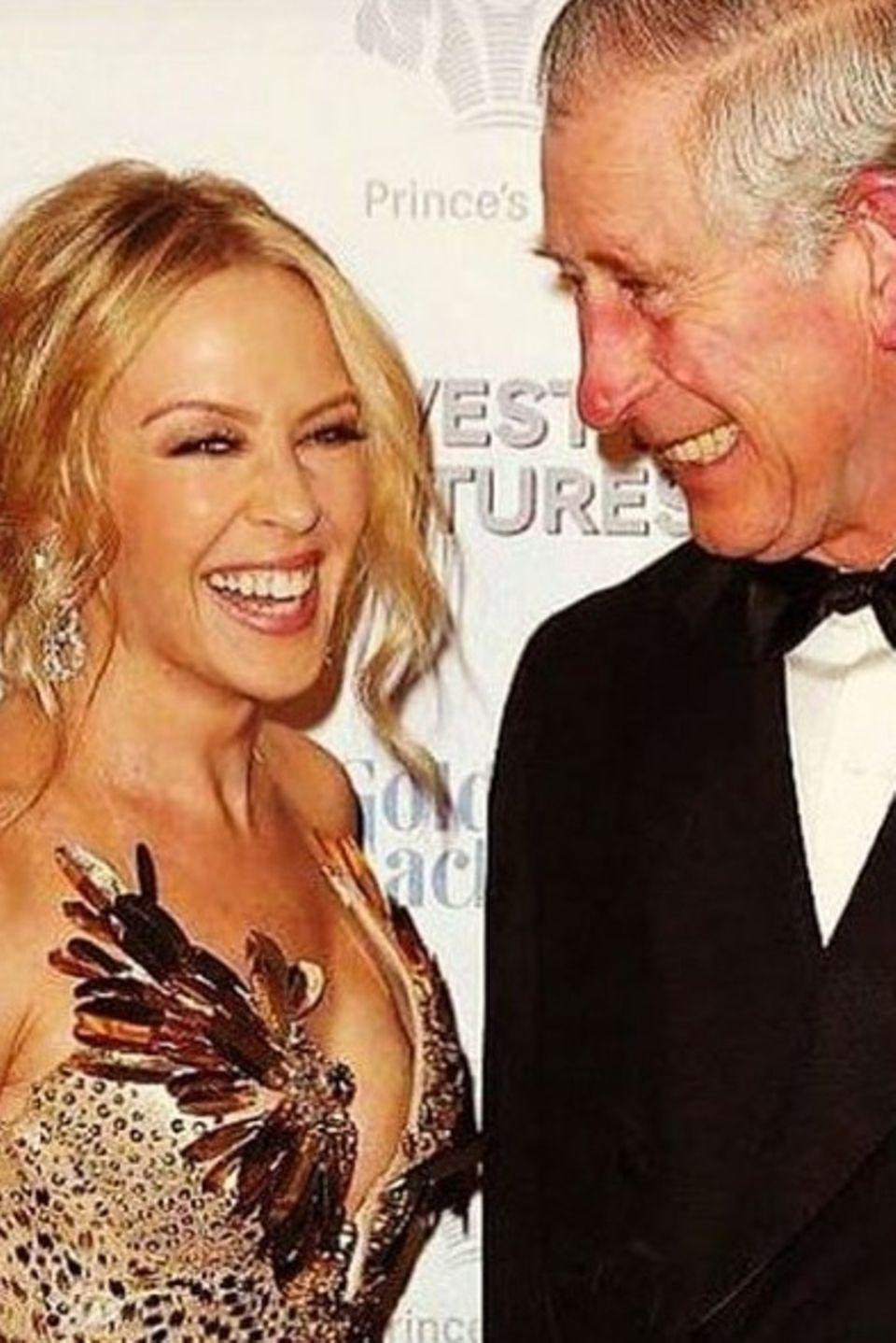 Februar 2016  Bei einer vom britischen Königshaus veranstalteten Charity-Gala halten Kylie Minogue und Prinz Charles ein charmantes Pläuschchen auf dem roten Teppich. Danach wird Kylie in ihrem goldenen Glitzerkleid eine heiße Performance auf der Bühne zeigen.