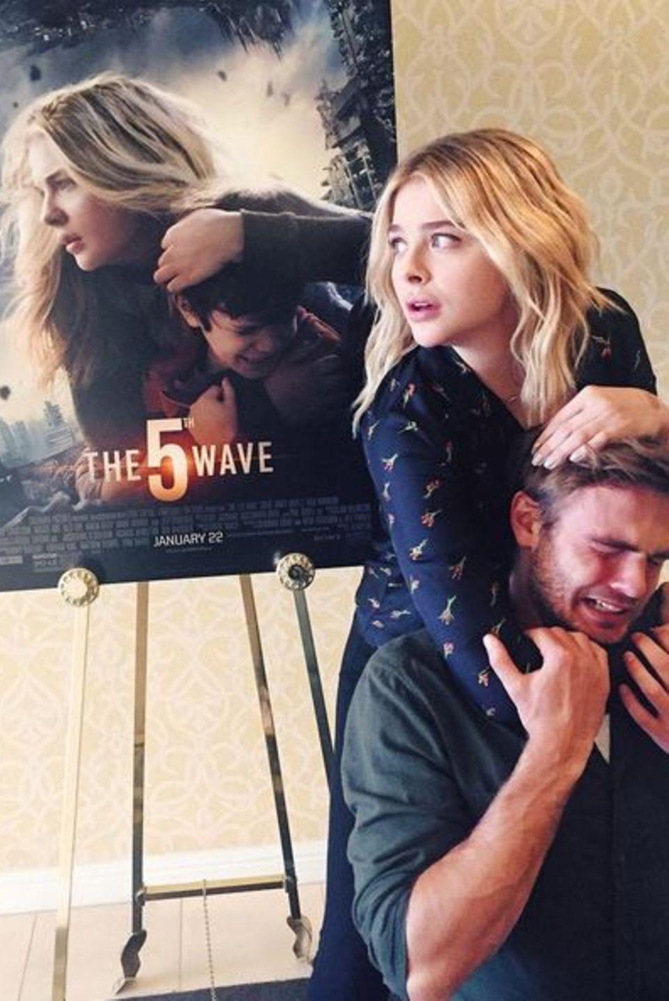 """Januar 2016  Die Schauspielerin Chloë Grace Moretz stellt das Plakat ihres aktuellen Films """"Die 5. Welle"""" mit ihrem Schauspielkollegen Alex Roe nach. Der läuft bereits preisverdächtig rot an. Der Film kommt am 14. Januar in die deutschen Kinos."""