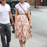 Stylischer Stil-Mix: Supermodel Karlie Kloss hat ihr weißes Shirt lässig nach oben geknotet. Durch die Kombination mit ihren weißen Sneakern wird der der Gesamtlook noch lässiger.