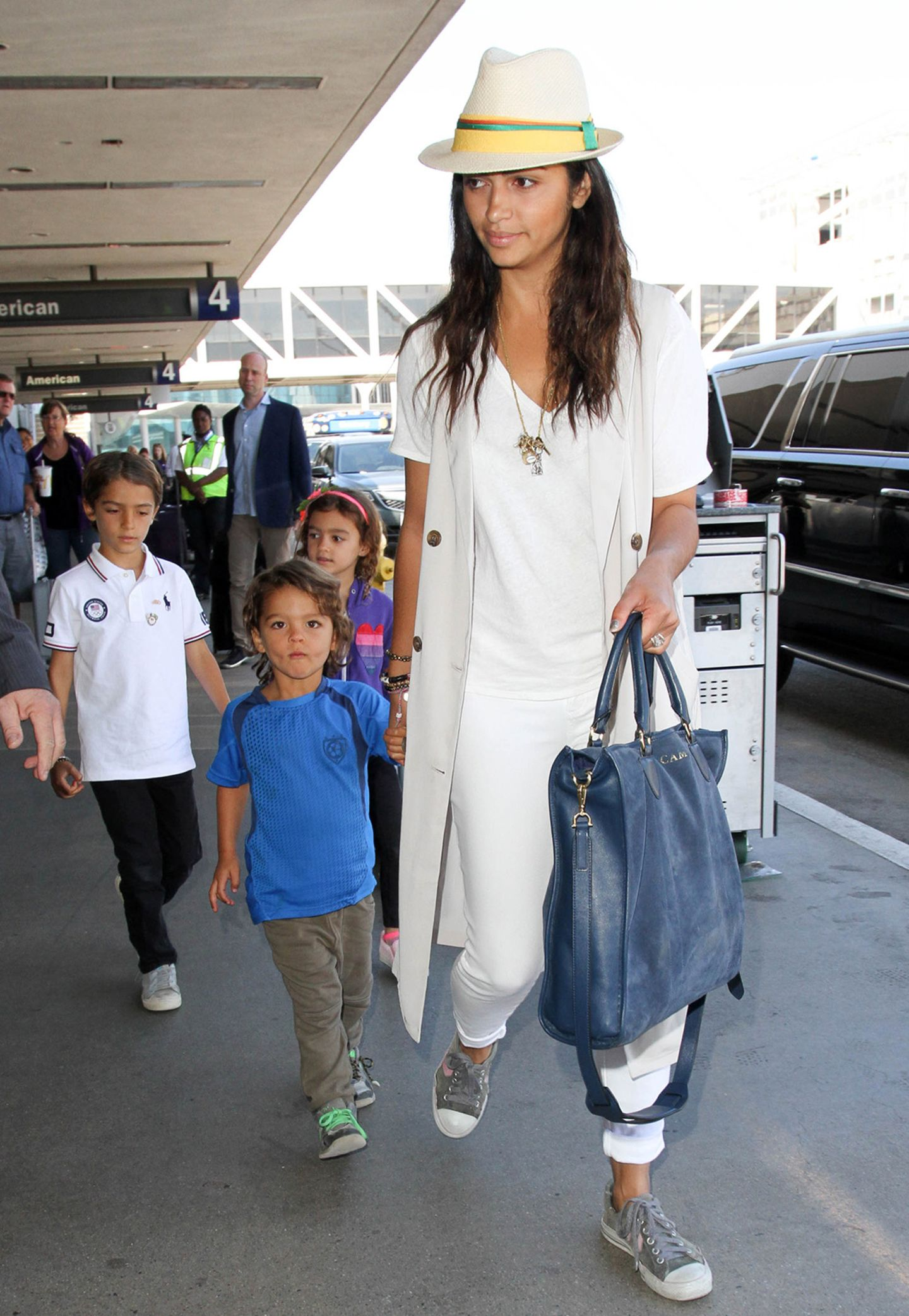 In sommerlichem Weiß zeigt sich Camila Alves mit ihren Kiddies ganz sportlich am Flughafen von L.A. Die elfenbeinfarbene, lange Weste bringt noch einen Hauch Eleganz in das Outfit.