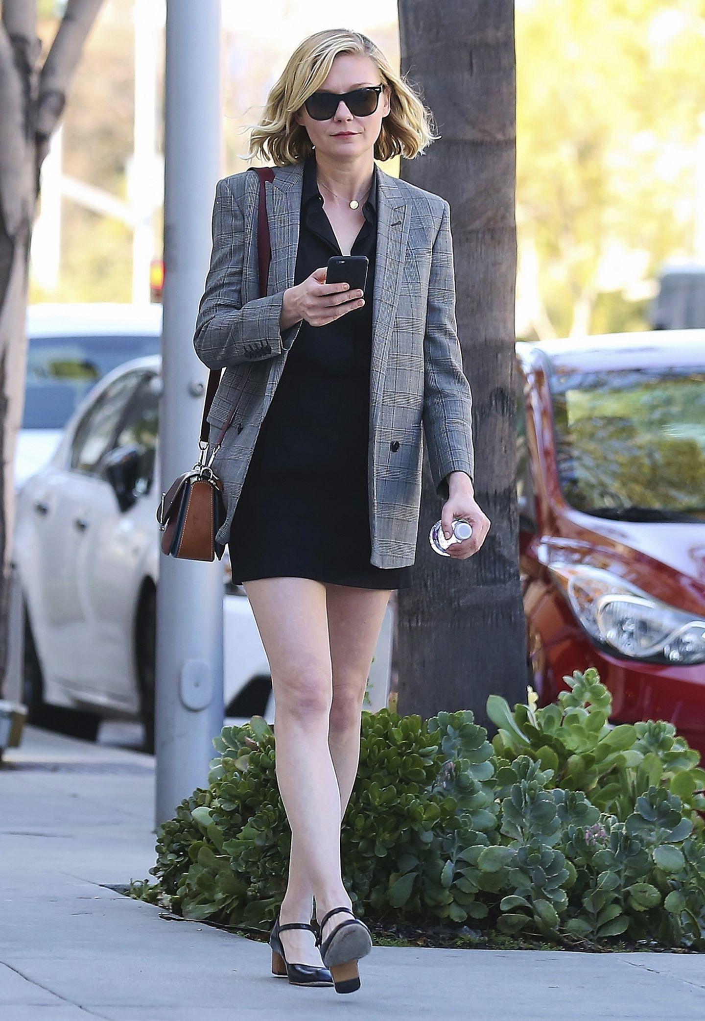 Kirsten Dunst spaziert in Blusenkleid und Oversize-Blazer durch Los Angeles. Besonders süß: die Schultertasche und bequemen Leder-Mary-Janes.