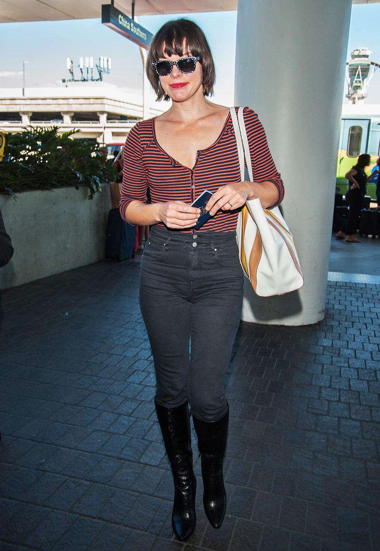 Am Flughafen unterwegs trägt Milla Jovovich zur dunklen High-Waist-Jeans ein bequemes Ringel-Shirt.