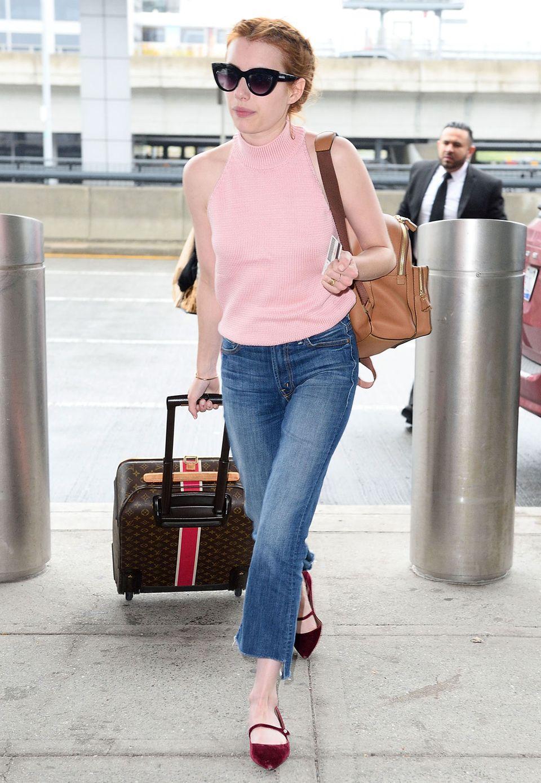 Zarte Farben im Romantic-Style, eine trendige 7/8-Flared-Jeans und edle Accessoires wie der Louis-Vuitton-Koffer und ein beiger Lederrucksack machen Emma Roberts' Look perfekt.