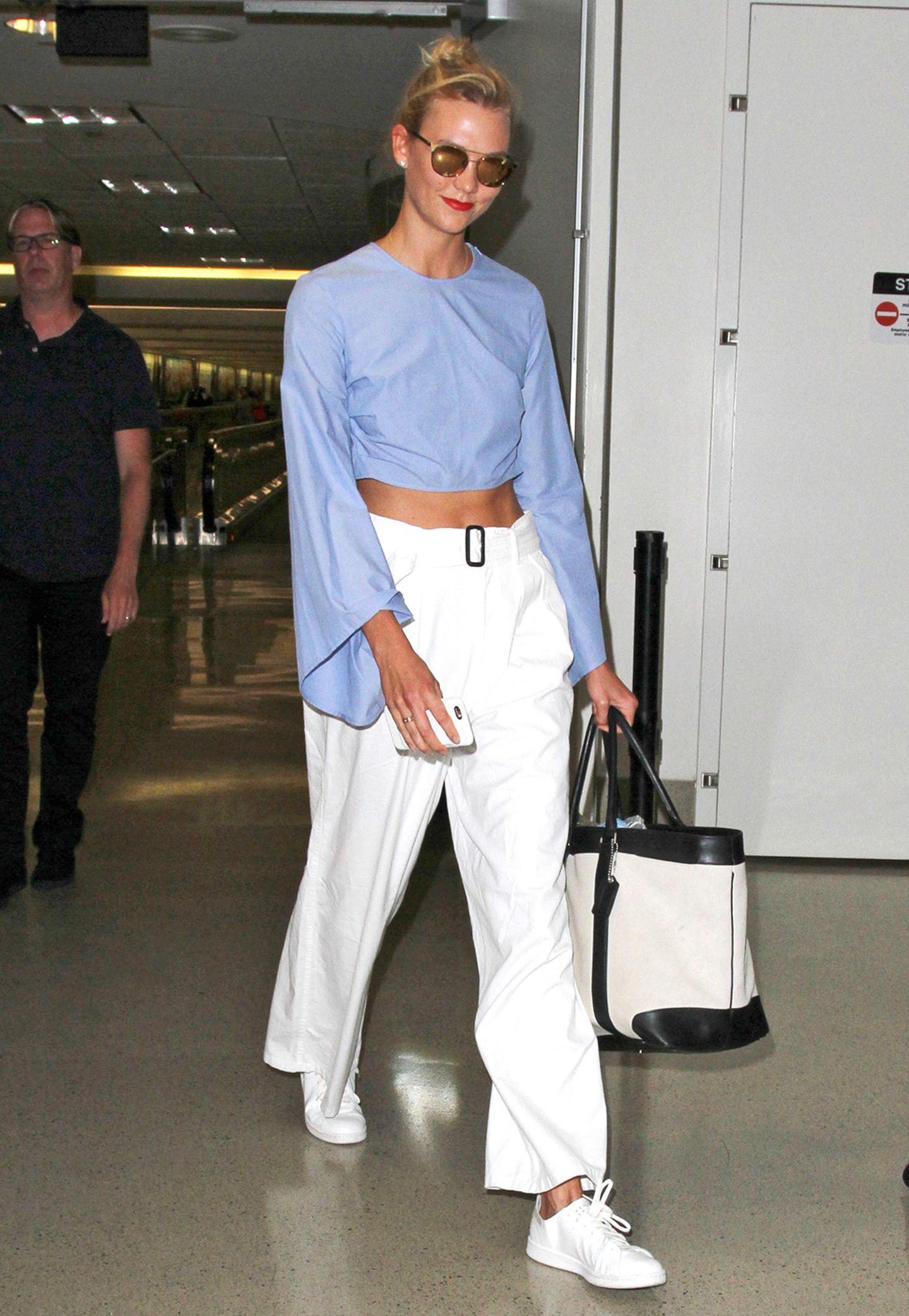 Supermodel Karlie Kloss präsentiert ihren trainierten Bauch zwischen hellblauer Bluse und bequemer, weißer Hose.