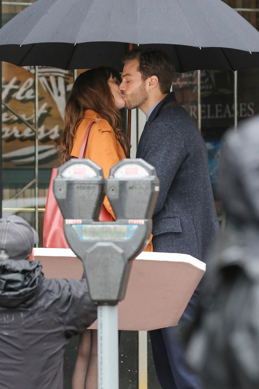 """1. März 2016: Endlich: Die Dreharbeiten zu """"Fifty Shades Darker"""" laufen und das erste Bild vom Set überrascht eher mit Romantik: Dakota Johnson und Jamie Dornan küssen sich unter einem Regenschirm. Bleibt zu hoffen, dass noch ein paar heißere Szenen gedreht werden."""